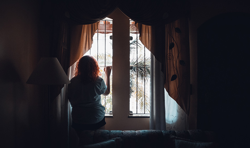 A women looking out her curtains